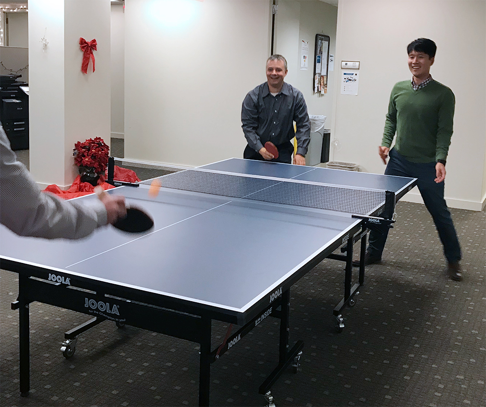 Savantage employees playing ping pong.